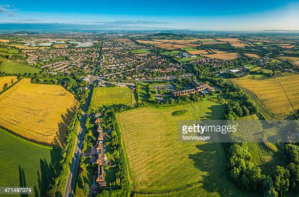 Aerial view over green fields pasture country town suburban housing