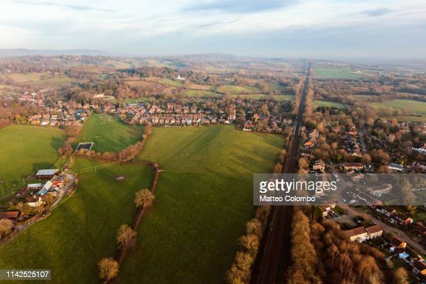 aerial view over green hills and suburb at sunset, england - surrey england stock pictures, royalty-free photos & images
