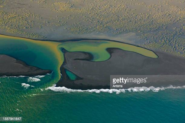 Aerial view over Landeyjarsandur showing beach with black volcanic sand and brown water laden with sediment flowing in sea in summer, Iceland.