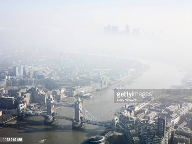 aerial view over london skyline in mist - isle of dogs london stock pictures, royalty-free photos & images