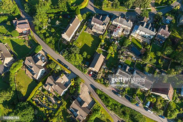 Aerial view over picturesque country homes green summer gardens
