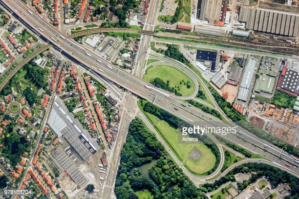 Aerial view over ribbon building and highway interchange / motorway interchange with slip roads leading to industrial estate.