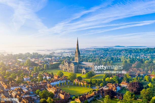 aerial view over salisbury and salisbury cathedral on a misty summer morning, salisbury, wiltshire, england, united kingdom, europe - サリスベリー ストックフォトと画像