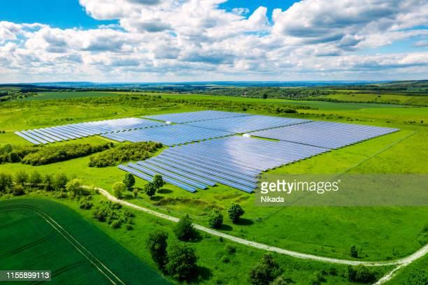 luftaufnahme über solarzellen energiebetrieb-betrieb in der landschaft - solarkraftwerk stock-fotos und bilder