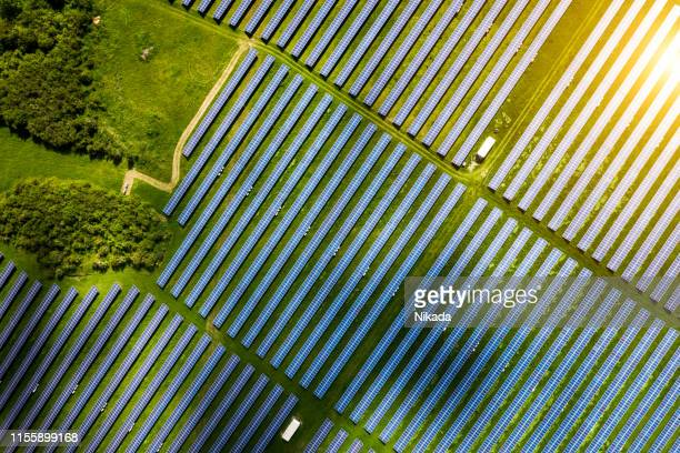 aerial view over solar cells energy farm in countryside landscape - solar powered station stock pictures, royalty-free photos & images