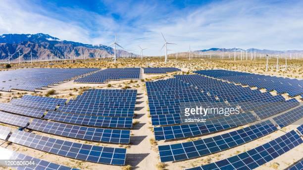 luftaufnahme über sonnenkollektoren und windmühlen - solarkraftwerk stock-fotos und bilder