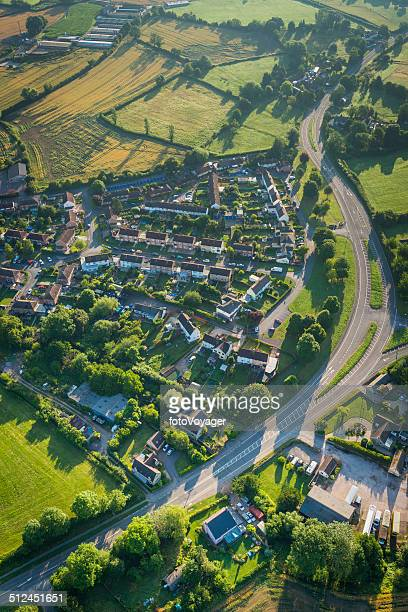 Aerial view over suburban village homes surrounded by green fields