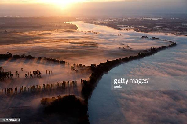 Aerial view over the Dordogne department covered in morning fog estuary of the Gironde Fields trees and hedges on the middle of the mist at sunrise