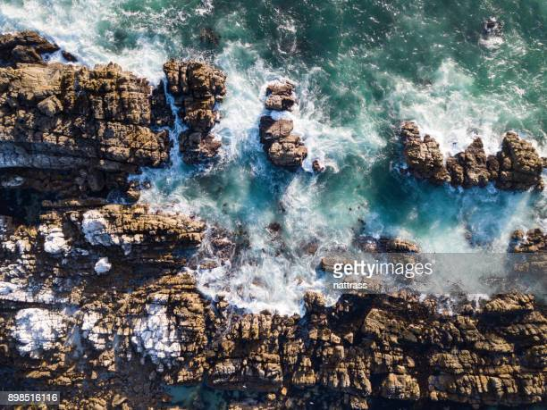 Aerial view over the sea crashing against the rocks