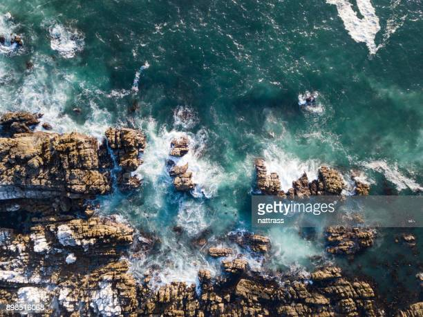 aerial view over the sea - rock overhang stock photos and pictures