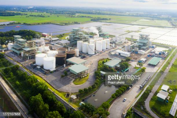 aerial view photo of industrial zone showing oil refinery with storage tank with solar farm power station for renewable energy supply. - factory stock pictures, royalty-free photos & images