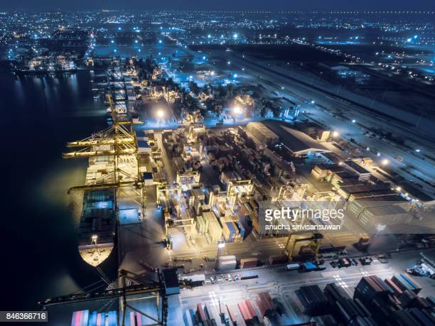 aerial view shipping dock have container ship and container at night .