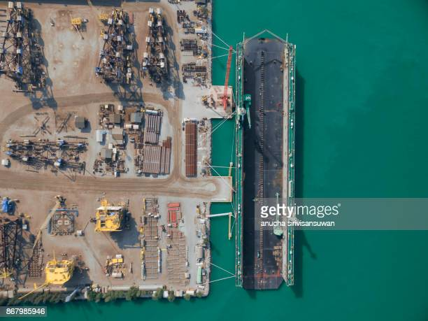 aerial view shipyard have crane machine and container ship in green sea . - religious occupation stock pictures, royalty-free photos & images