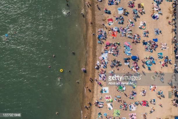 aerial view showing a crowd of people sunbathing on a beach, southend-on-sea, essex, united kingdom - southend on sea stock pictures, royalty-free photos & images
