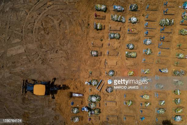 Aerial view showing a tractor digging graves in a new area of the Nossa Senhora Aparecida, where COVID-19 victims are buried, in Manaus, Brazil, on...