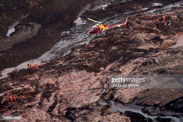 TOPSHOT Aerial view showing firemen looking for people in heavy machinery and a locomotive after the collapse of a dam which belonged to Brazil's...