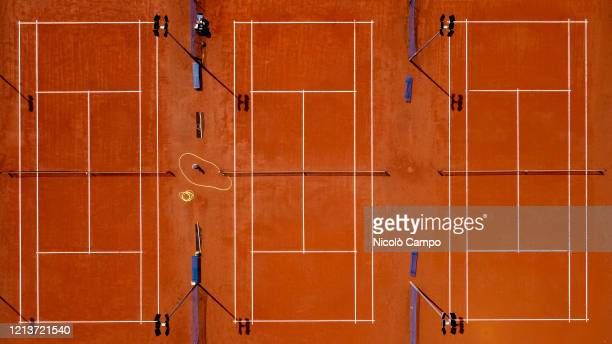 Aerial view shows three empty clay tennis courts. The lockdown caused by the COVID-19 coronavirus emergency banned all sports activities.