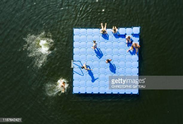 Aerial view taken on July 25, 2019 shows bathers on and around a pontoon floating on the Altwarmbuechener See lake in Hanover, northern Germany,...