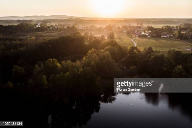 Aerial view to a lake with two swans and a village during sunset on October 14 2018 in See Germany
