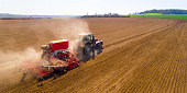 Aerial view to a Tractor with sowing machine working on a  field. Agriculture from above.