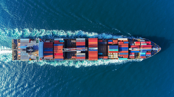 Aerial view Top speed with beautiful wave of container ship full load container with crane loading container for logistics import  export or transportation concept background. 1066762856