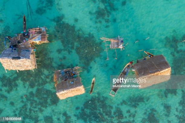 aerial view using drone the sea gypsy stilt house at water village located in tatagan mabul island, semporna, sabah, malaysia. - mabul island stock photos and pictures
