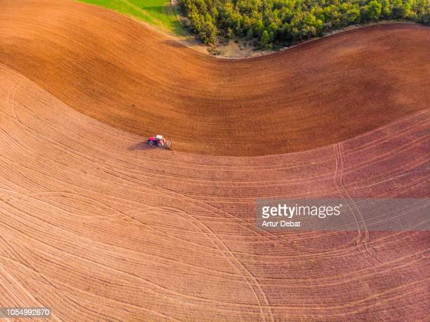 aerial view with drone of tractor plowing the land in the countryside. - cataluña fotografías e imágenes de stock