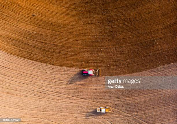 aerial view with drone of tractor plowing the land in the countryside. - drone stock pictures, royalty-free photos & images