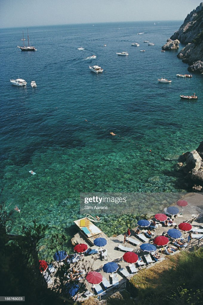 Aerial view with sunbathers and parasols and, dotted with yachts and small boats, the waters off the coast of Porto Ercole, Italy, in July 1991. The image was taken from Hotel Il Pellicano.