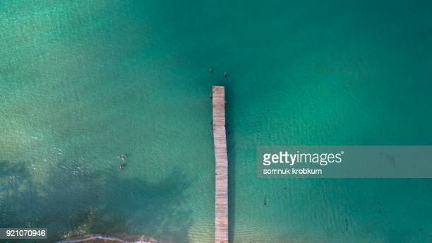 Aerial view wood pier with clear sea water in summer by drone