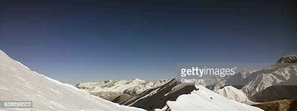 Aerial Views of an Alpine valley and Mountains covered in fresh Snow