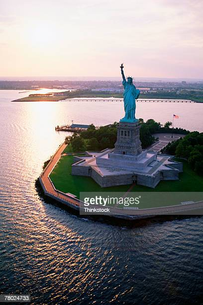 Aerial wide shot of the Statue of Liberty with the sun reflecting in the water near sunset.