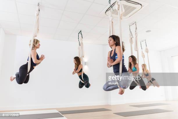 Aerial yoga teacher guiding students in different poses