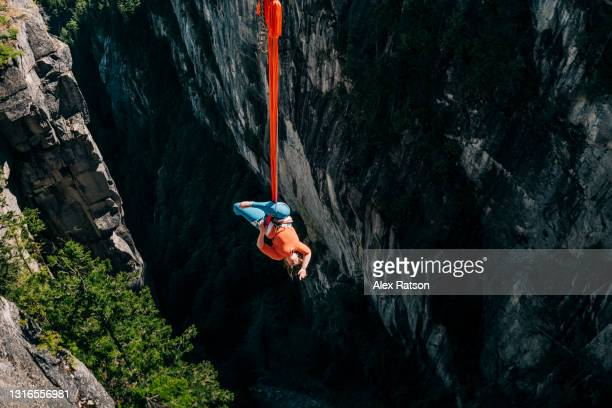 aerialist hangs upside down from silk high up on rock face - hanging stock pictures, royalty-free photos & images