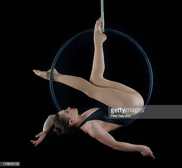 aerialist performing on hoop in front of black background - 空中曲芸師 ストックフォトと画像