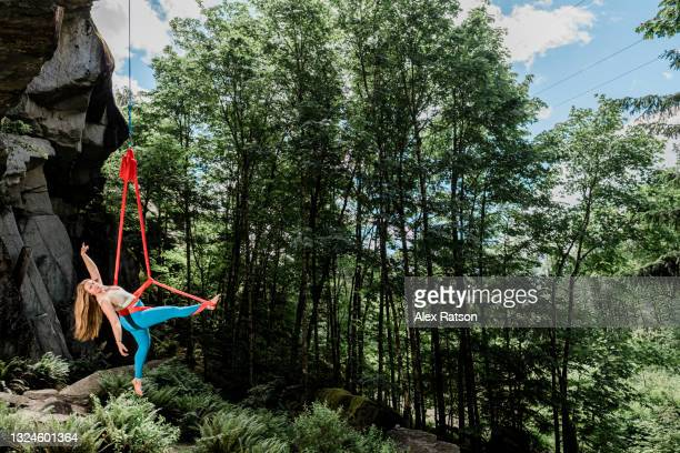 aerialist performs on a silk under a overhanging cliff - 空中曲芸師 ストックフォトと画像