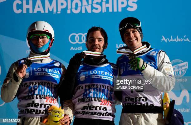 Aerials World Champion 2017 US skier Jonathon Lillis celebrates his victory with silver medallist Chinese skier Guangpu Qi and bronze medallist...