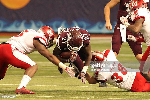 Aeris Williams of Mississippi State is brought down by Miami defenders led by Brad Koenig during the St Pete Bowl between the Miami RedHawks and the...