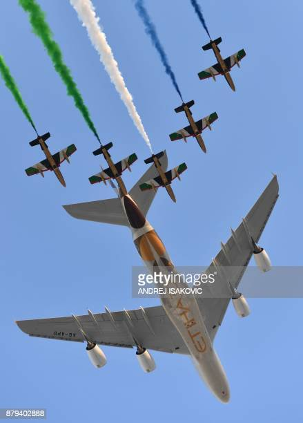 Aermacchi MB339 jets from UAE's AlFursan display team perform with an Etihad Airways' Airbus A380 before the start of the Abu Dhabi Formula One Grand...
