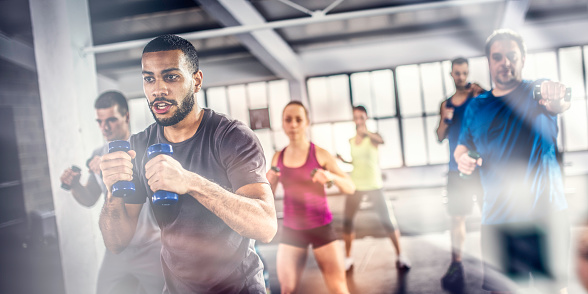 Aerobics class shadow boxing with dumbbells 1018647930