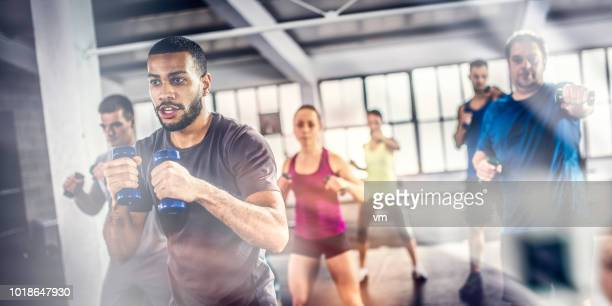 aerobics class shadow boxing with dumbbells - fat black man stock photos and pictures