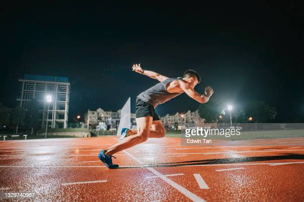 aerodynamic asian chinese male athletes sprint running at track and run towards finishing line at track and field stadium track rainy night - forward athlete stock pictures, royalty-free photos & images