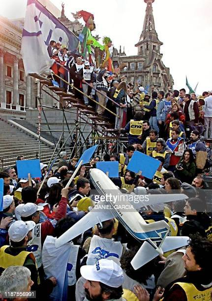 Aerolineas Argentinas workers hold a Boeing 737 model and form part of the Argentine Workers Central Union march 09 August as they arrive in Buenos...