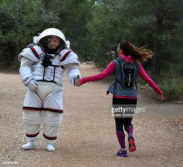 Aeronautics and Space engineer at France's Compagnie Maritime d'Expertises or Comex Arnaud Prost meets with a jogger as he tests on the ground the...