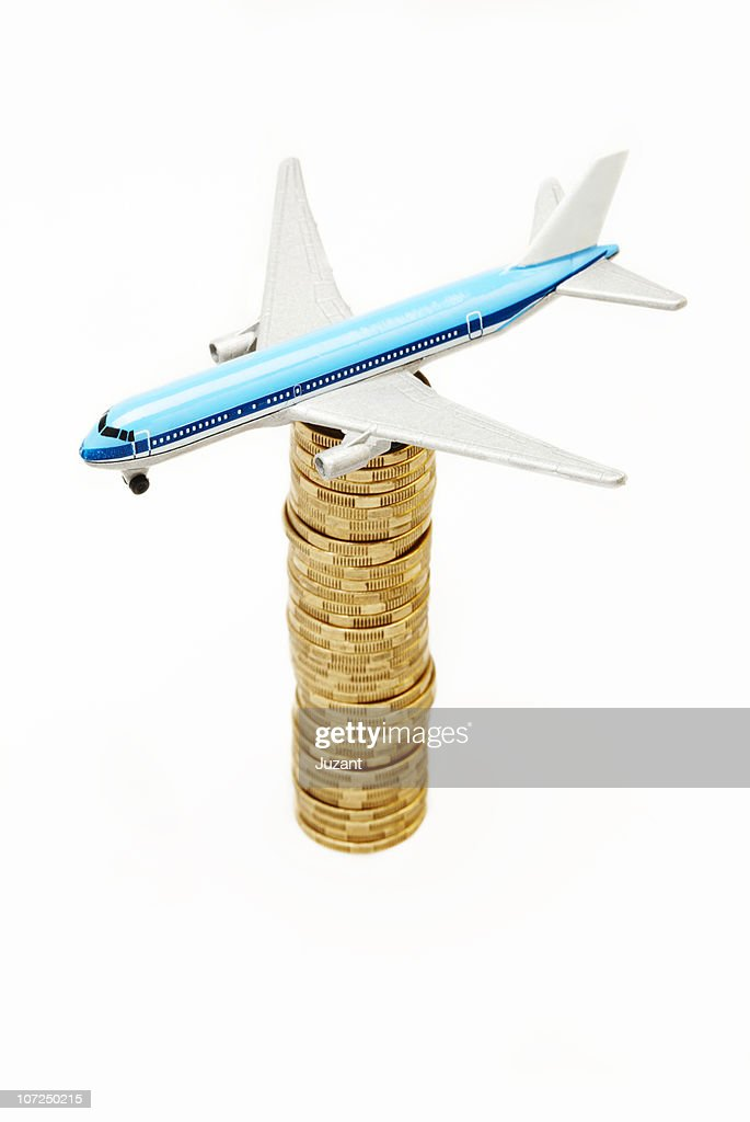 Aeroplane Balancing On A Pile Of Coins Stock Photo - Getty