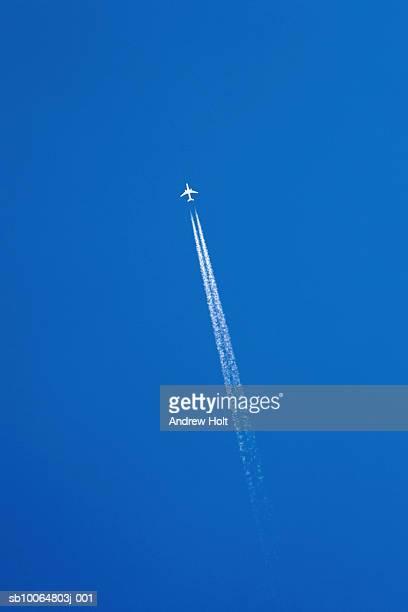 aeroplane leaving vapour trail in clear blue sky, low angle view - trainée d'avion photos et images de collection