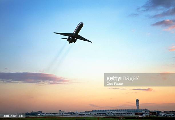 Aeroplane taking off from airport, low angle view, dusk