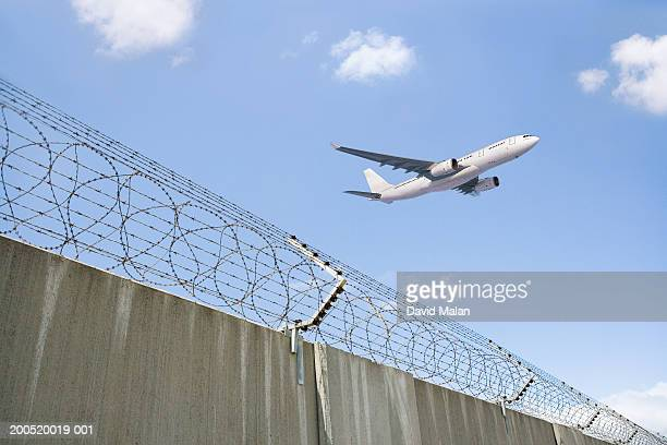 Aeroplane taking off, with security fence in foreground