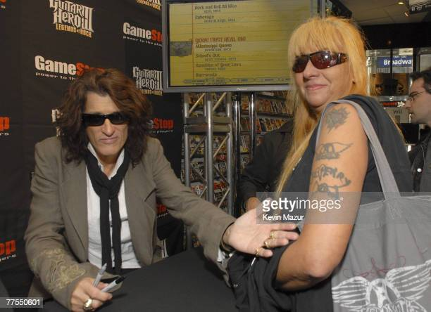 Aerosmith Guitarist Joe Perry and a fan with an Aerosmith and Joe Perry tatoo at Game Stop in celebration of the launch of Guitar Hero III Legends of...