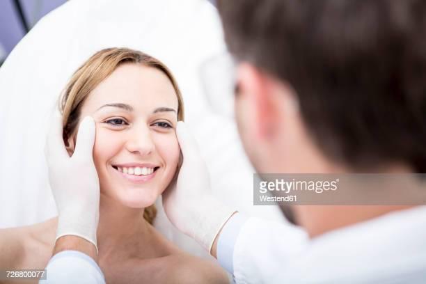 aesthetic surgery, doctor looking at woman - kosmetische behandlung stock-fotos und bilder